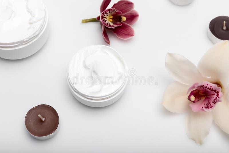 Crema orgánica en envases con las orquídeas y velas aisladas en blanco fotos de archivo