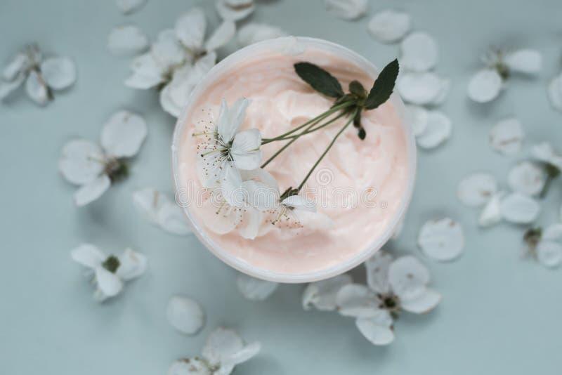 Crema per il corpo e petali bianchi fotografia stock