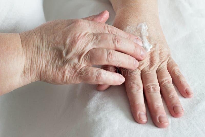 Crema per le mani anziana dello sfregamento della donna, fondo bianco, primo piano, cosmetici fotografia stock