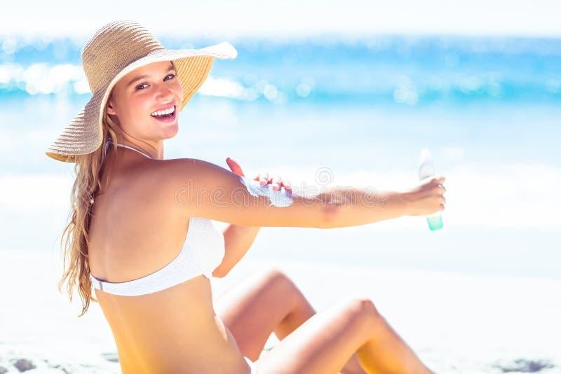 Crema solare di diffusione della donna bionda graziosa su lei armi fotografia stock libera da diritti