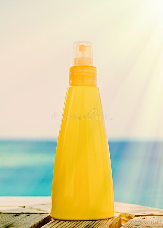 crema solare sulla spiaggia - concetto di cura dei cosmetici, di estate, di feste, della pelle e del corpo immagini stock libere da diritti