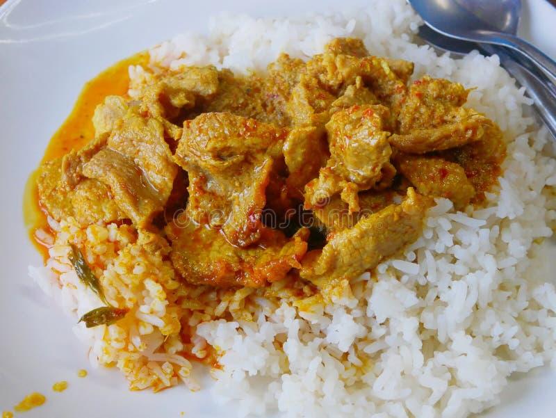 Crema tailandesa de coco, salada y dulce, curry rojo tailandés con cerdo Panang Moo sobre arroz blanco suave imagenes de archivo