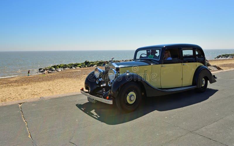 Crema y negro Rolls Royce Motor Car del vintage que es conducida a lo largo de la 'promenade' de la orilla del mar imagenes de archivo
