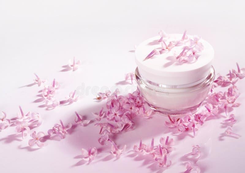 Crema y pétalos de flores rosadas fotos de archivo libres de regalías