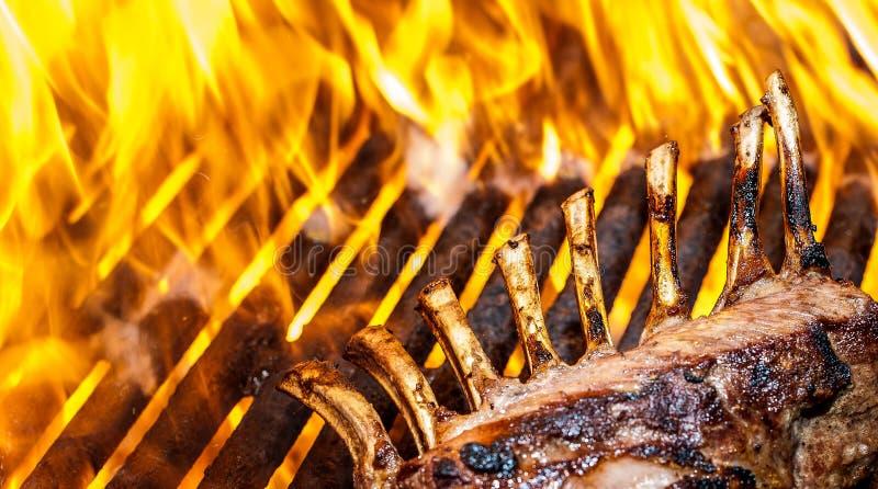 Cremagliera dell'agnello francese sulla griglia con le fiamme fotografia stock