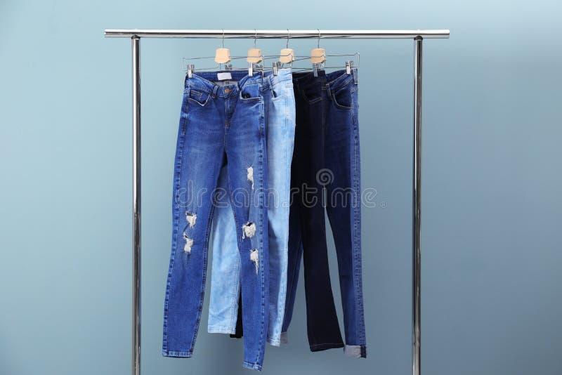 Cremalheira com calças de brim à moda imagens de stock