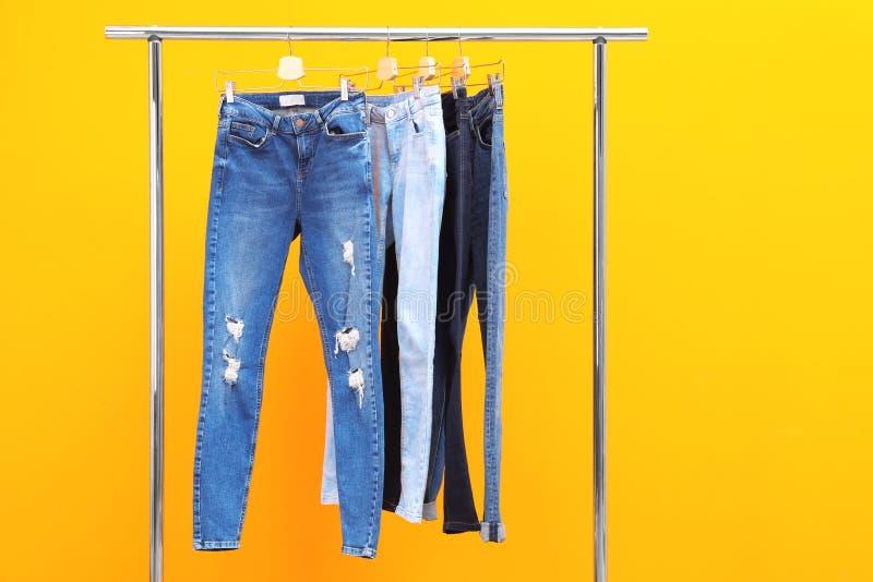 Cremalheira com calças de brim à moda fotos de stock