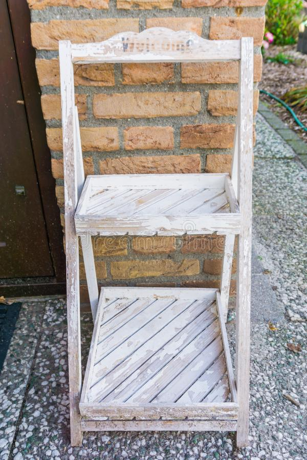 Cremalheira de armário branca resistida de madeira pequena vazia com textura do fundo do sinal bem-vindo fotografia de stock