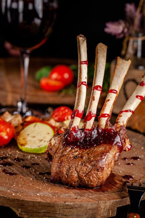 Cremalheira de cordeiro com vegetais e molho grelhados da framboesa Pratos de serviço em uma placa de madeira com um vidro do vin foto de stock