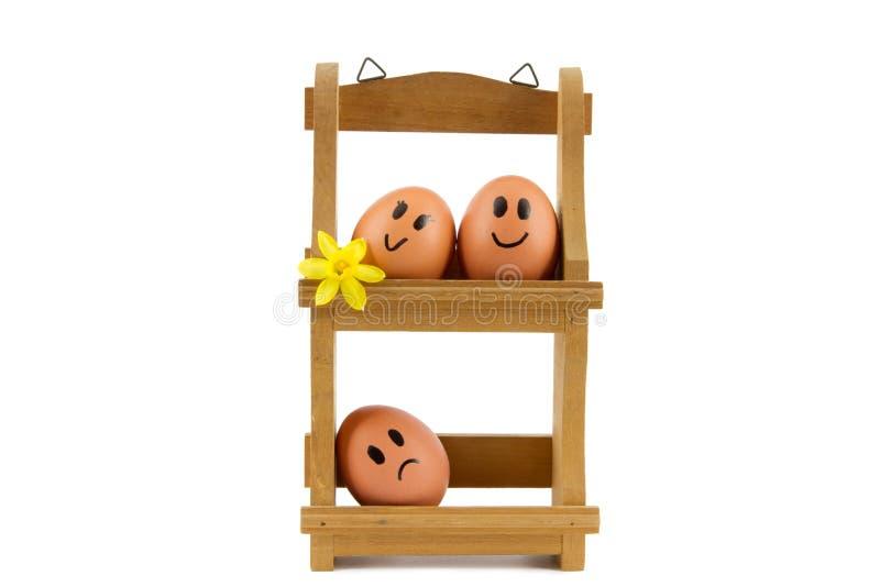 Cremalheira de madeira do ovo com os três ovos com expressões faciais fotografia de stock royalty free