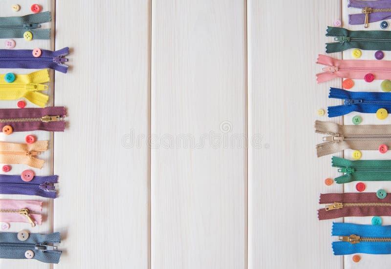 Cremalleras y botones coloridos en la tabla de madera blanca Estilo de la vendimia costura Copie el espacio imagenes de archivo