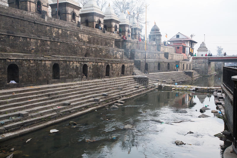 Cremation ceremony along the holy Bagmati River in Bhasmeshvar Ghat at Pashupatinath temple. KATHMANDU, NEPAL - DEC 20: During the cremation ceremony along the stock image