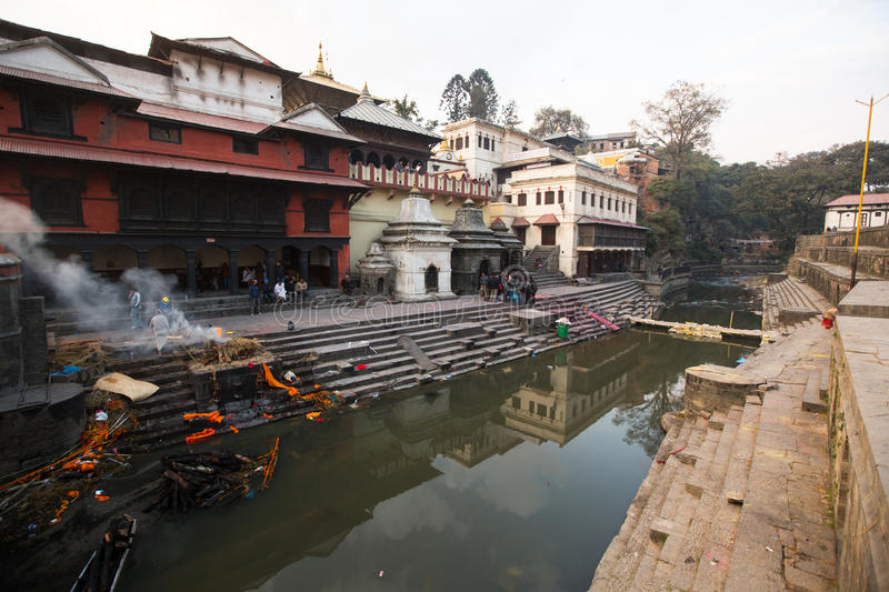 During the cremation ceremony along the holy Bagmati River in Bhasmeshvar Ghat at Pashupatinath temple. KATHMANDU, NEPAL - DEC 20: During the cremation ceremony royalty free stock image