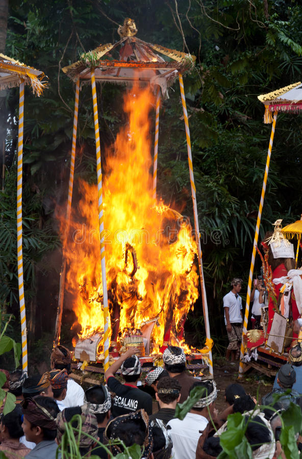 Cremation Ceremony: funeral pyres on fire. PENESTANAN - BALI - INDONESIA, 14th JULY 2010 - BALINESE CREMATION CEREMONY: the funeral pyres in the form of a lemu stock image
