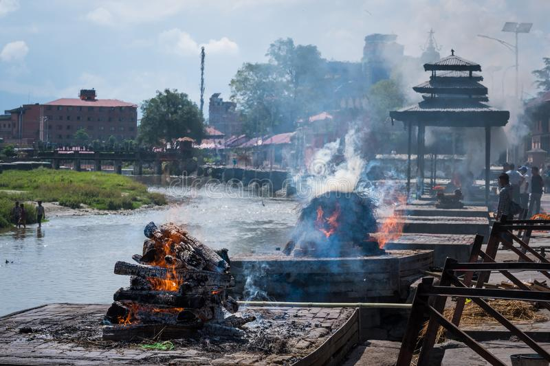 Pashupatinath temple cremations on the Bagmati River. Cremation ceremony at Pashupatinath temple on the Bagmati River royalty free stock photography