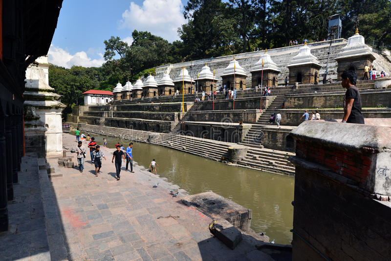 Cremation ghats and ceremony along the holy Bagmati River at Pashupatinath Temple. PASHUPATINATH - OCT 8: Cremation ghats and ceremony along the holy Bagmati royalty free stock photo