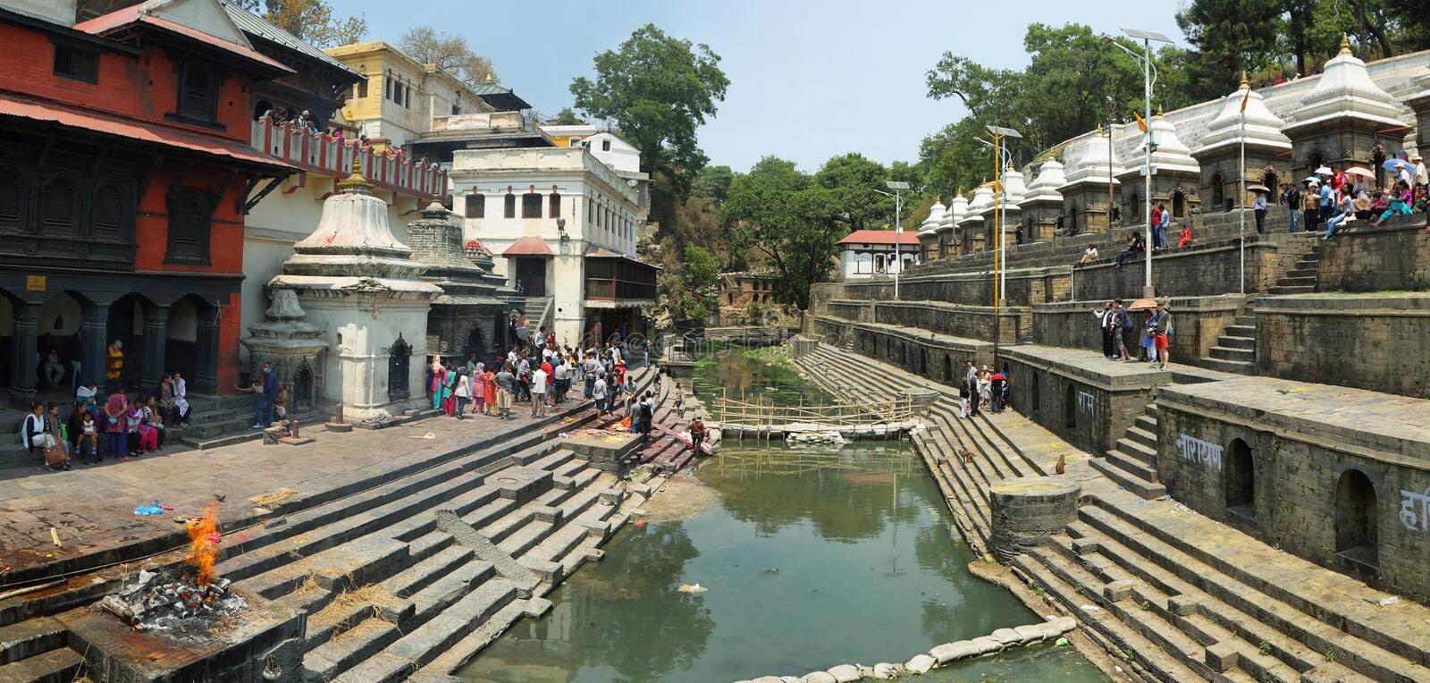 Cremation in sacred Hindu temple dedicated to Pashupatinath in Kathmandu, Nepal. KATHMANDU, NEPAL - APRIL 20, 2016: people around covered dead before cremation royalty free stock photo