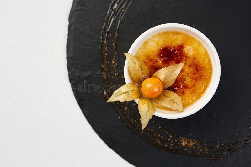 Creme brulée com Physalis e açúcar mascavado Sobremesa do creme brulée no xisto preto imagem de stock