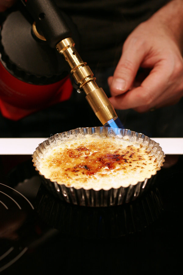 Creme brulee with blowtorch stock images