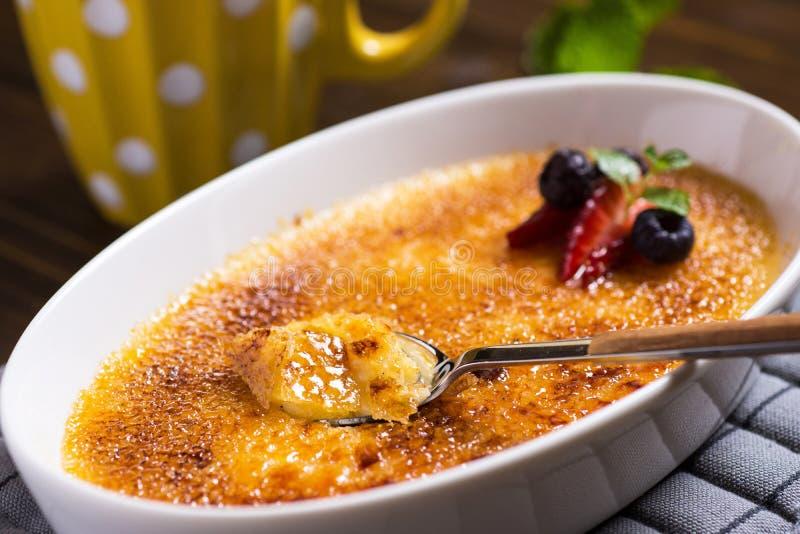 Creme Brulee deser z Karmelizującym cukierem, truskawką, czarną jagodą i Świeżymi Nowymi liśćmi, zdjęcie royalty free