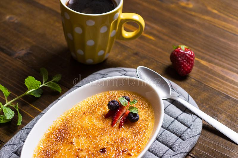 Creme Brulee Dessert with Caramelised Sugar, Strawberry, Blueberry and Fresh Mint Leaves. Sweet Creme Brulee Dessert with Caramelised Sugar, Strawberry royalty free stock image