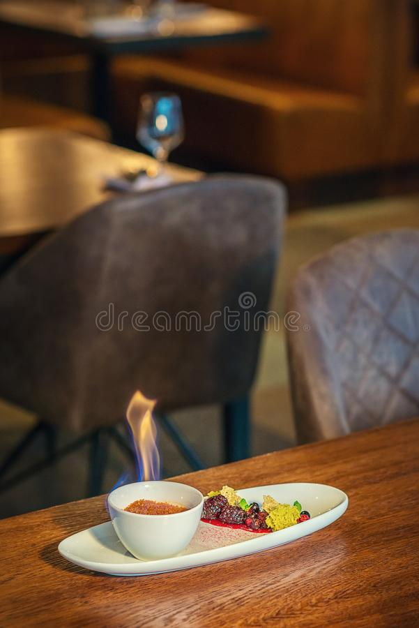 Creme brulee with hot forest fruit served on white plate in modern restaurant, product photography for gastronomy stock photography