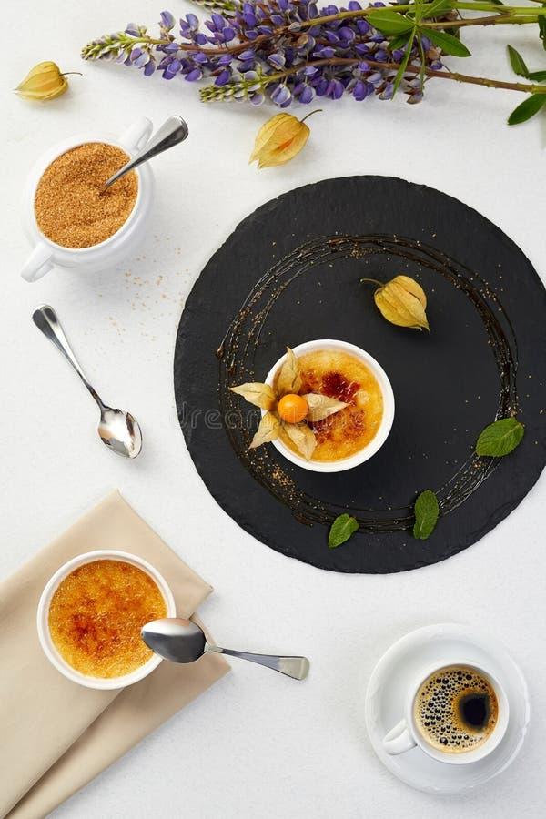 Creme brulee mit Physalis und braunem Zucker Creme- bruleenachtisch mit Lavendel und Kaffee auf schwarzem Schiefer lizenzfreie stockfotografie