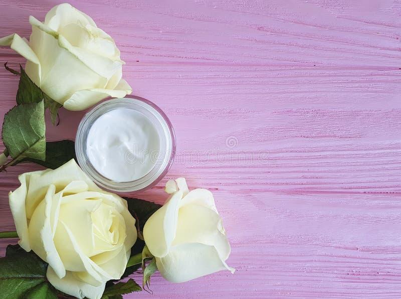Creme cosmético antienvelhecimento, careon decorado da mão da pele da rosa do amarelo um rosa de madeira foto de stock