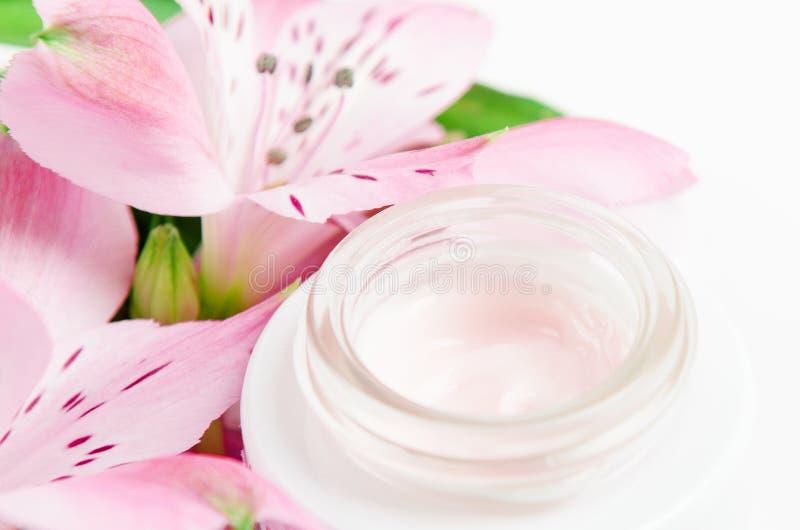 Creme de cara no frasco branco em um fundo branco com flores cor-de-rosa Cosm?ticos naturais do conceito, beleza org?nica, flor imagens de stock