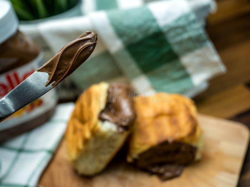 Creme der süßen Schokolade im Messer und in Brot angefüllt mit lizenzfreie stockfotografie