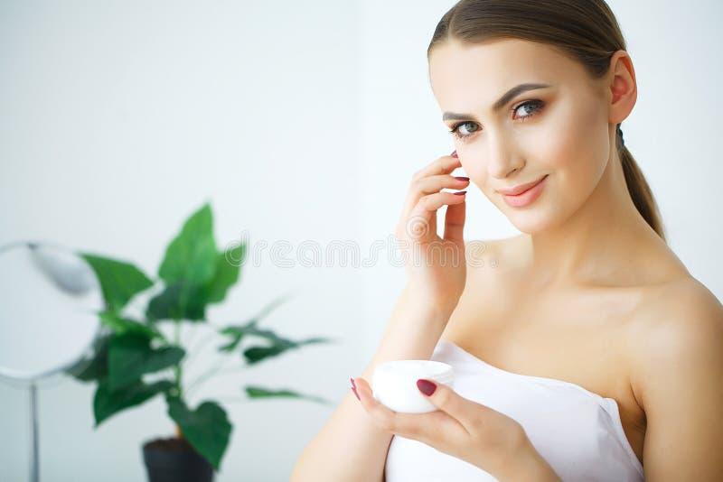 Creme do cosmético da posse da mulher Modelo bonito dos jovens da cara imagens de stock royalty free
