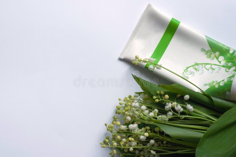 Creme e lírio cosméticos das flores do vale no fundo branco imagens de stock