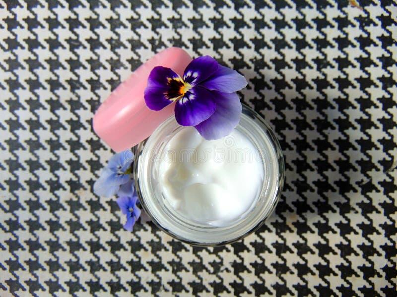 Creme facial para bons cuidados com a pele com flores roxas imagens de stock