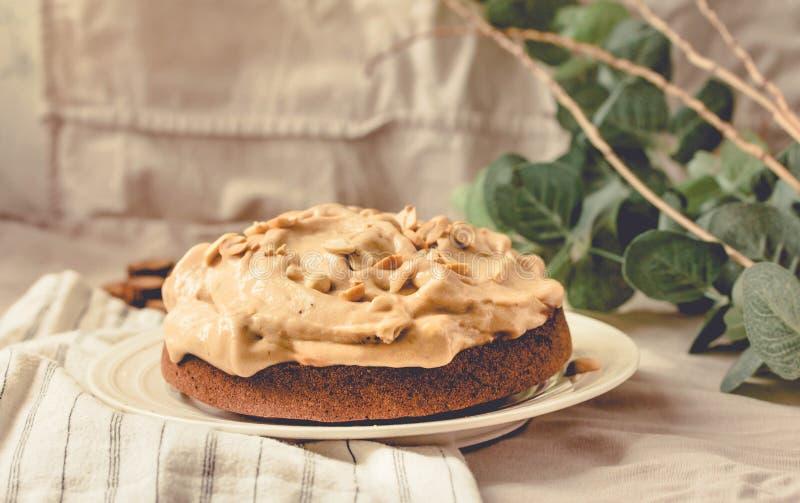 Creme kichert Torte Schokoladen-Schwamm-Kuchen gef?llt mit Schlagsahne und Erdn?ssen Auf wei?em Leinentischdeckenhintergrund tone lizenzfreies stockbild