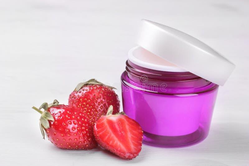 Creme mit Erdbeerauszug auf einem weißen hölzernen Hintergrund stockbild