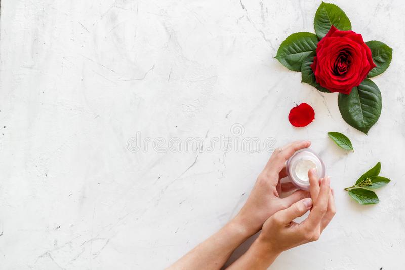 Creme nas mãos para cosméticos orgânicos com a flor cor-de-rosa no espaço de mármore branco da opinião superior do fundo para o t imagens de stock