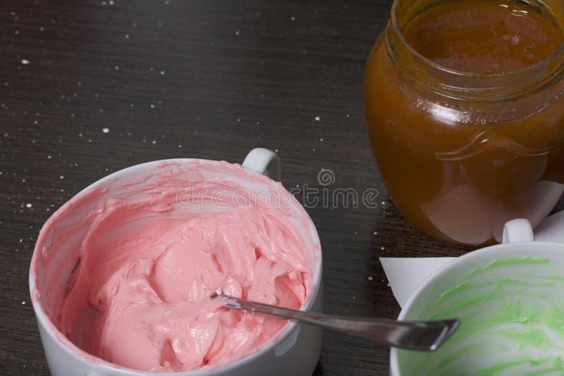 Creme von verschiedenen Farben für die Verzierung von Kuchen Korb Ist in der Nähe ein Glas Stau stockfoto