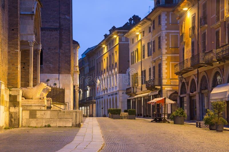CREMONA, ITALIA - 24 MAGGIO 2016: La via di vecchia città con i leoni verso ovest del portale della cattedrale nel crepuscolo di  fotografia stock