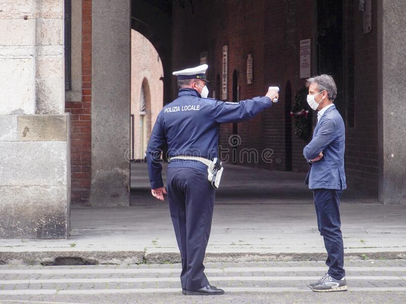Cremona, Lombardy, Italy - 13 th may 2020 - Local police officer measuring adult man body temperature with infrared thermometer royalty free stock images