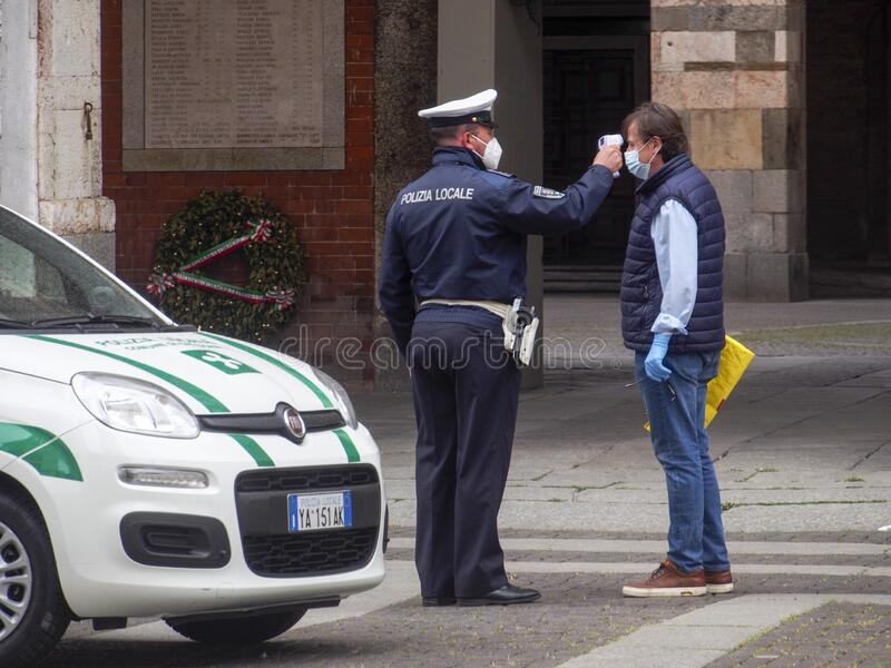 Cremona, Lombardy, Italy - 13 th may 2020 - Local police officer measuring adult man body temperature with infrared thermometer stock image