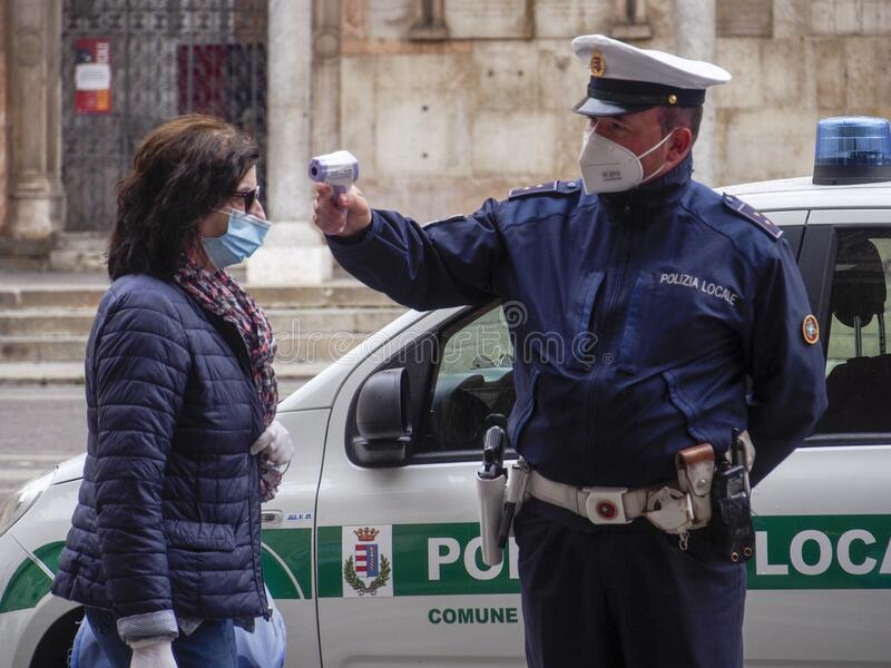 Cremona, Lombardy, Italy - 13 th may 2020 - Local police officer measuring adult woman body temperature with infrared royalty free stock photography