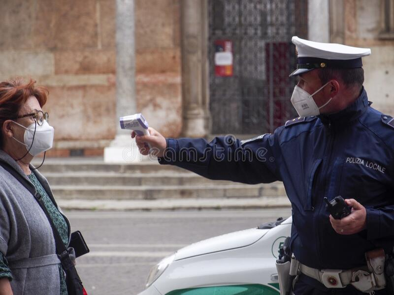 Cremona, Lombardy, Italy - 13 th may 2020 - Local police officer measuring adult woman body temperature with infrared royalty free stock photos