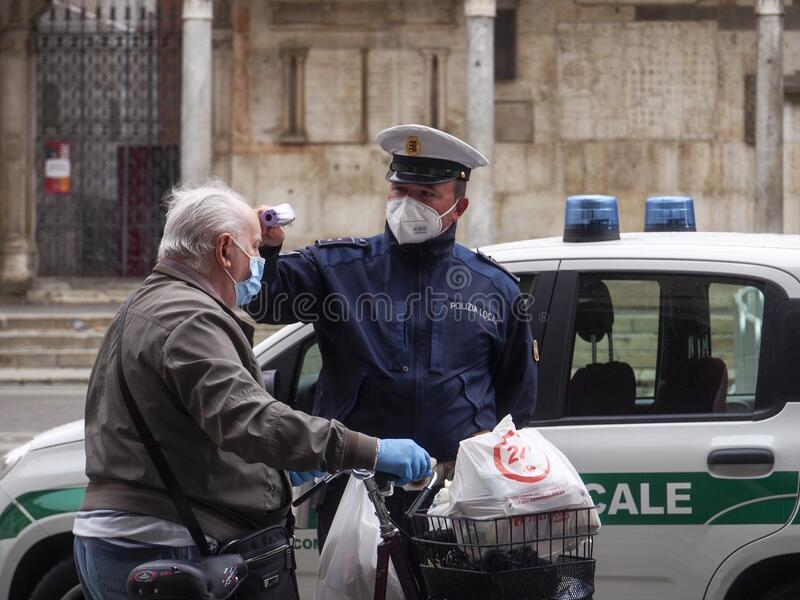 Cremona, Lombardy, Italy - 13 th may 2020 - Local police officer measuring senior adult body temperature with infrared royalty free stock photography
