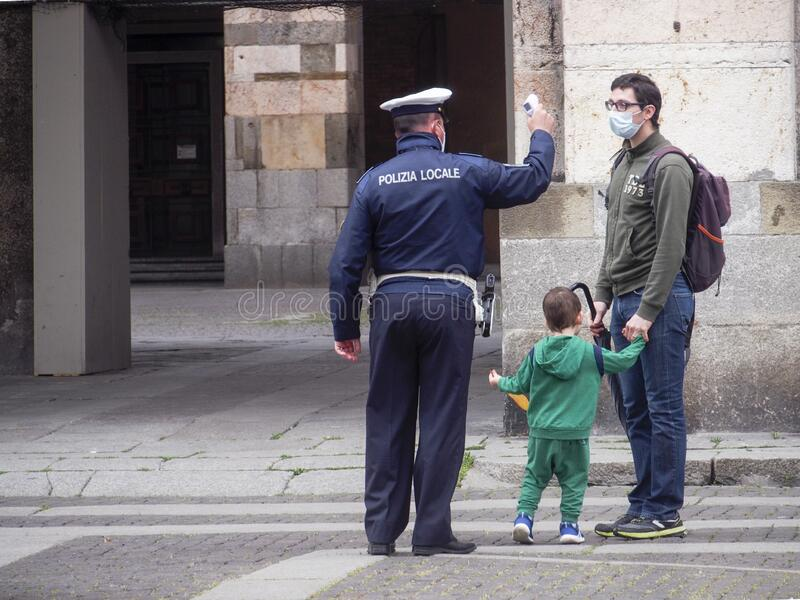 Cremona, Lombardy, Italy - 13 th may 2020 - Local police officer measuring young man and son body temperature with infrared royalty free stock image