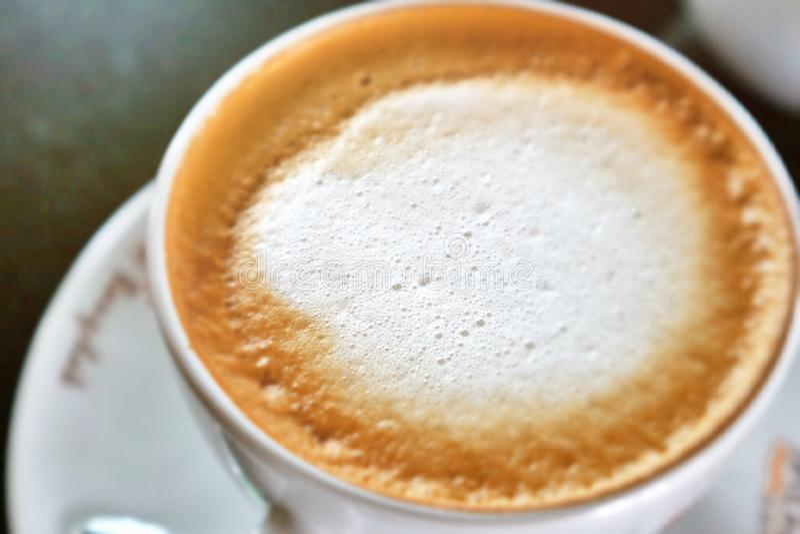 Cremoso di caffè sul fondo della sfuocatura fotografia stock libera da diritti