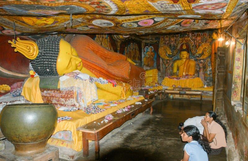 Crentes que rezam no monastério de Aluvihara de Matale em Sri Lanka imagens de stock