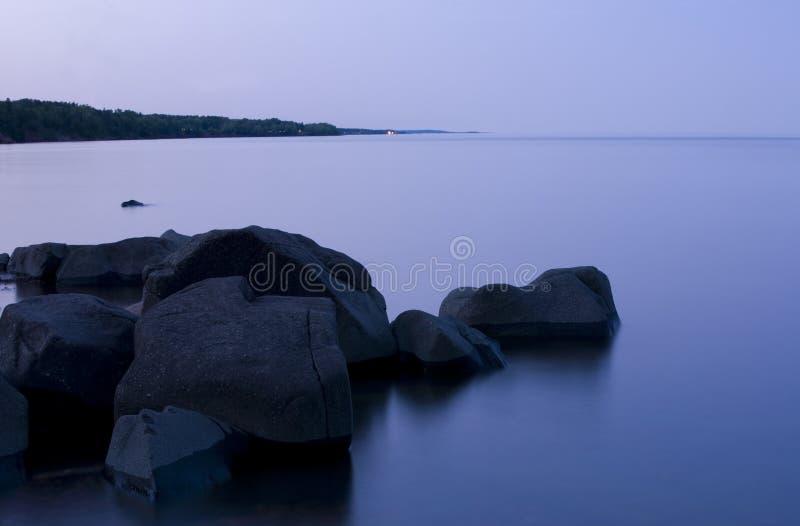 Crepúsculo, água de vidro, e pedra fotografia de stock