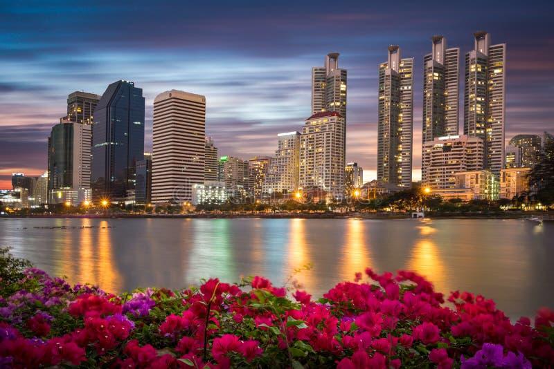 Crepúsculo de Bangkok, edificio del negocio con la luz y reflexión, visión desde el parque de Benjakitti imagen de archivo