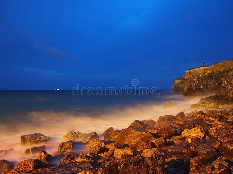 Crepúsculo em rochas e em ondas do beira-mar imagem de stock