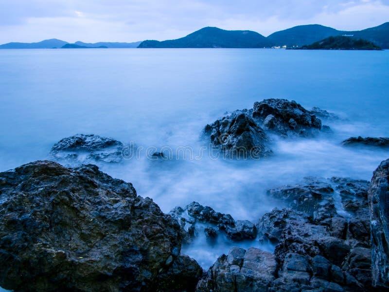 Crepúsculo em rochas e em ondas do beira-mar fotos de stock